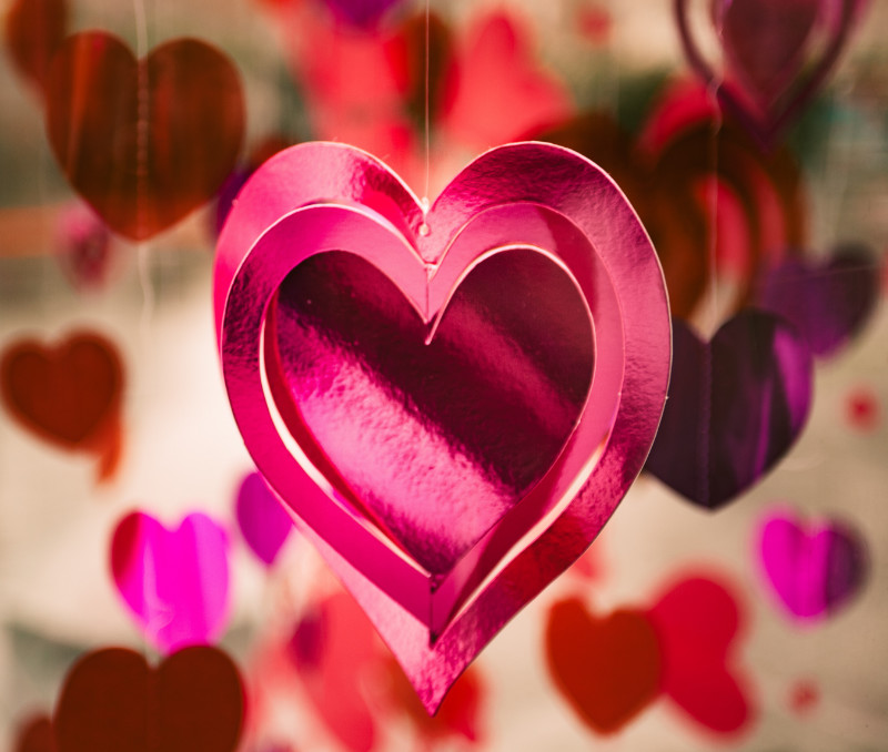 Pink and red heart-shaped cutouts hanging from ceiling