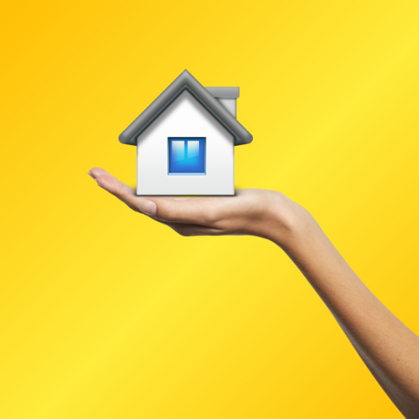 a hand holds up a small model of a house against a yellow background