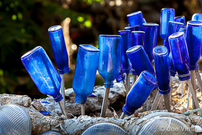 "Bottles ""blossom"" in a planter made of car headlights."