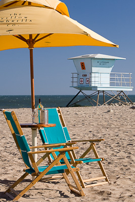 Yellow beach umbrella and chairs on the Ventura State Beach with a lifeguard tower in the background