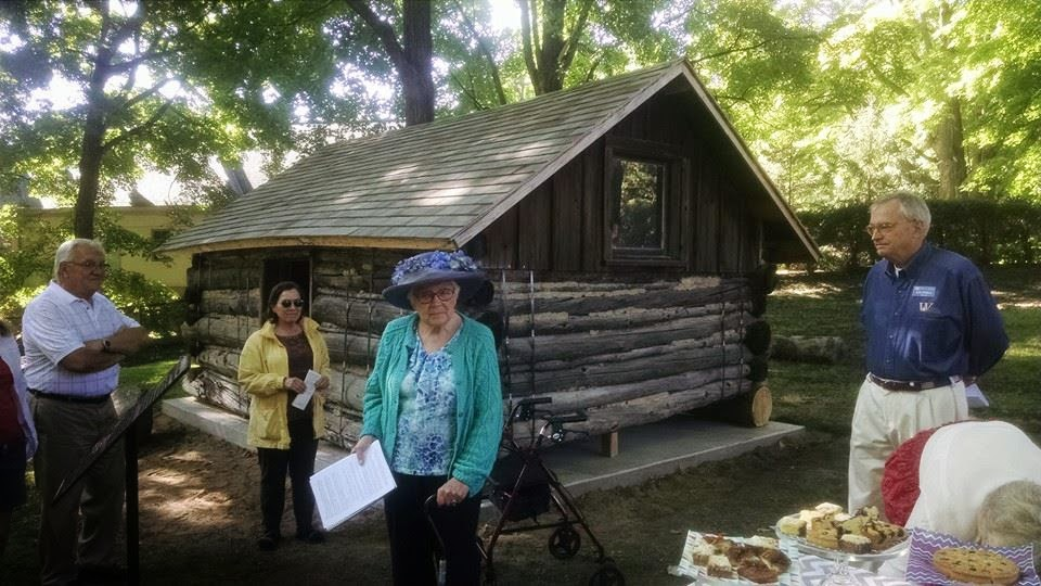 Irene Stemmer & Ken Willcox stand in front of the Wayzata Trappers Cabin